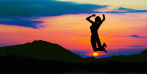 Silhouette of happy woman jumping at sunset